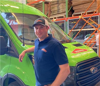 Brendan posing with arm on SERVPRO Van in a blue shirt and hat
