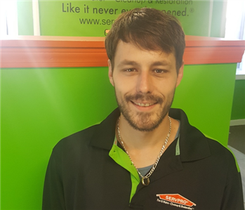servpro employee in front of servpro sign