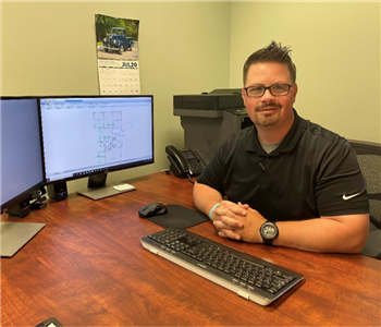 Chris posing at his desk with monitors  Chris St. Onge       Chris is our General Manager at SERVPRO of Merrimack and is Inst