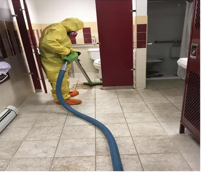 technician in yellow cleaning up sewage in men's locker room